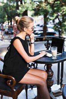 黒のショートドレスで美しい女性は、カフェテリアのテラスでノートパソコンとテーブルで働いています。彼女は忙しいようです。
