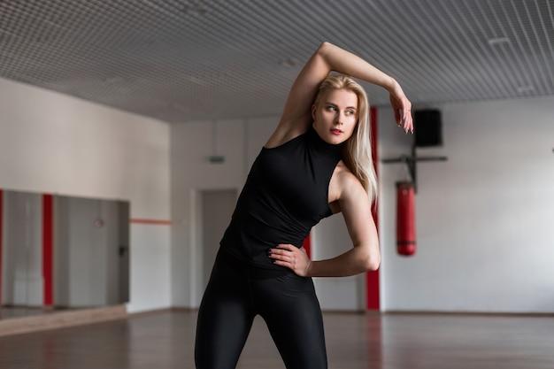Красивая женщина в черной спортивной одежде держит равновесие, стоя в спортивном классе