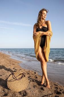 Красивая женщина в черном купальнике на пляже