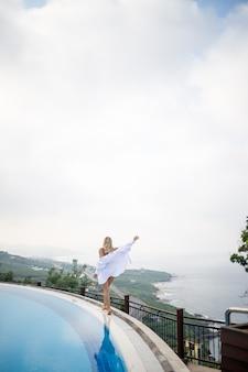 Красивая женщина в черном купальнике позирует возле открытого бассейна с видом на море
