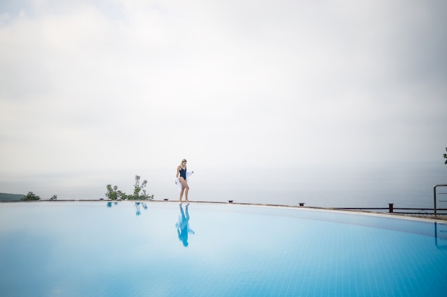海の見える屋外プールの近くでポーズをとって黒い水着の美しい女性