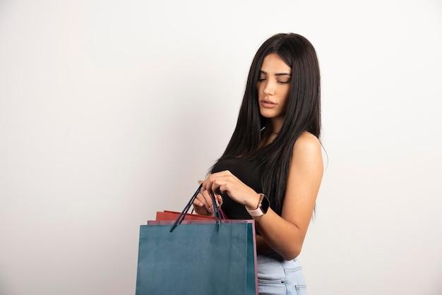 ショッピングバッグを見ている黒いトップの美しい女性。高品質の写真