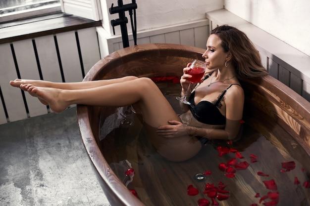 Красивая женщина в черном нижнем белье, отдыхая в ванной комнате. влюбленная женщина отдыхает, цветы и лепестки роз
