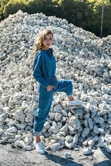 大きな白い根の石の間にポーズをとる青いオーバーオールの美しい女性。キャリア。ライフスタイル