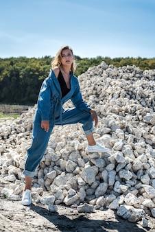 大きな白い根の石の間にポーズをとる青いオーバーオールの美しい女性。キャリア