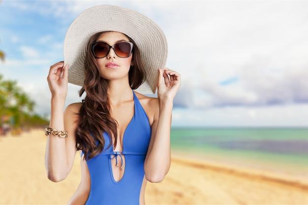Красивая женщина в синем купальнике на фоне тропического моря