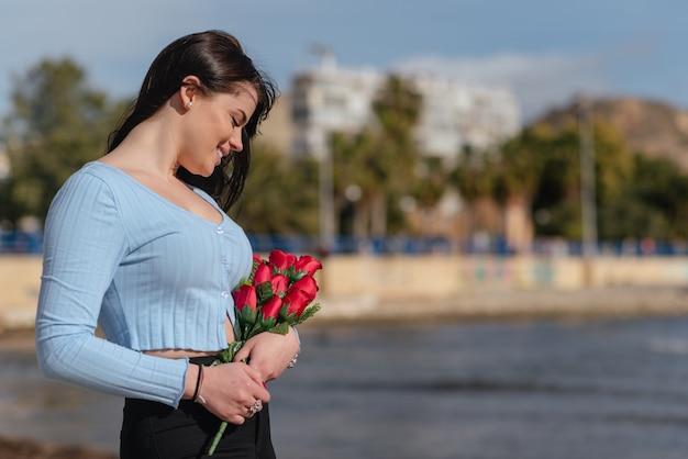 Красивая женщина в синей футболке и черных брюках держит букет красных роз на открытом воздухе в день святого валентина
