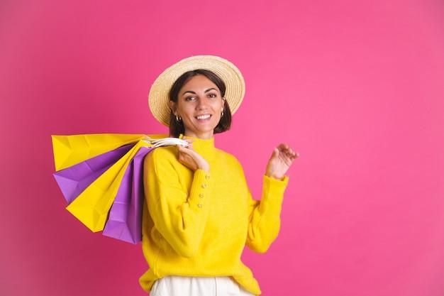 Красивая женщина в ярко-желтом свитере и соломенной шляпе на розовых сумках для покупок счастливое возбужденное радостное изолированное пространство для текста