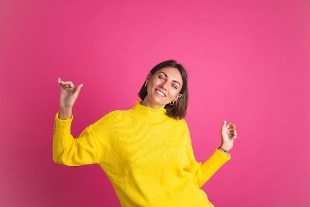Красивая женщина в ярко-желтом свитере изолирована на розовой счастливой взволнованной танцующей подвижной улыбке