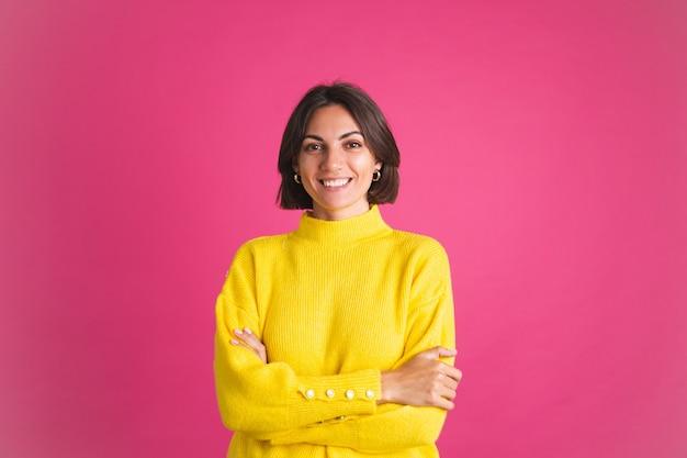 Красивая женщина в ярко-желтом свитере, изолированном на розовом, смотрит вперед с уверенной улыбкой Premium Фотографии