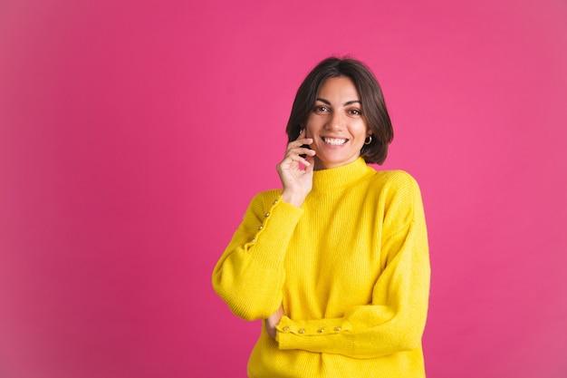 Красивая женщина в ярко-желтом свитере, изолированном на розовом, смотрит вперед с уверенной улыбкой