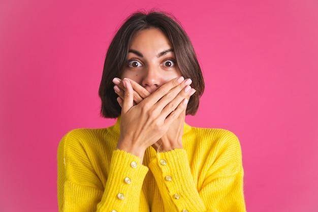 Красивая женщина в ярко-желтом свитере изолирована на розовом в шоке, прикрывает рот руками