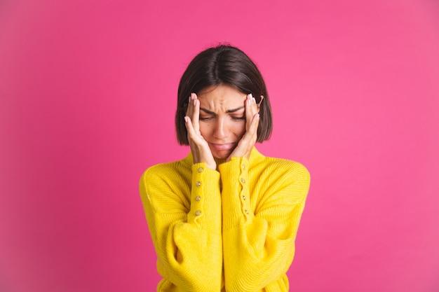 Красивая женщина в ярко-желтом свитере изолирована на розовой стрессовой плачущей депрессии