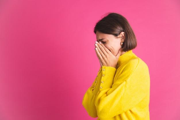 ピンクのストレスの多い泣いているうつ病に分離された明るい黄色のセーターを着た美しい女性