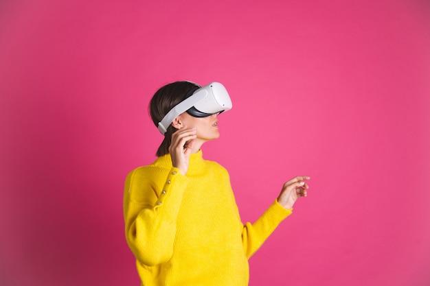 Красивая женщина в ярко-желтом свитере на розовом в очках виртуальной реальности счастливая, взволнованная, радостная прикосновение воздуха
