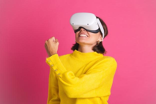 Красивая женщина в ярко-желтом свитере на розовом в очках виртуальной реальности счастлива прыгает, сжимая кулак, жест победителя