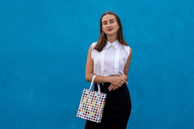 青い背景で隔離の買い物袋を保持しているビジネス服の美しい女性。ショッピングライフスタイル、ブラックフライデーセール