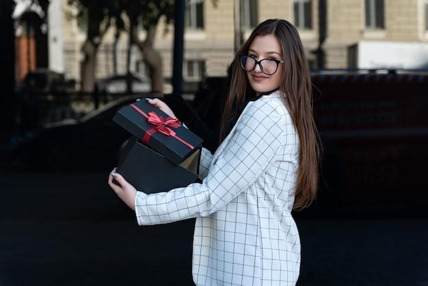 Красивая женщина в деловом костюме и очках открывает подарок в удивлении. молодая женщина открыла черную подарочную коробку.