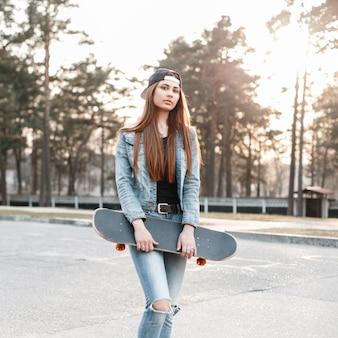 Красивая женщина в кепке и джинсовой одежде держит скейтборд в весенний солнечный день