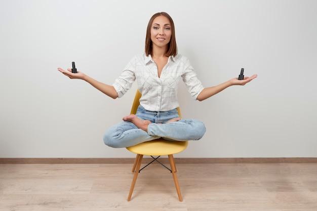 Красивая женщина в повседневной одежде, сидя на стуле, держа бутылки лака для ногтей над белой спиной ...