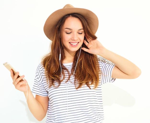 Красивая женщина в повседневной хипстерской летней одежде без макияжа в коричневой шляпе слушает музыку в телефоне с наушниками на белом