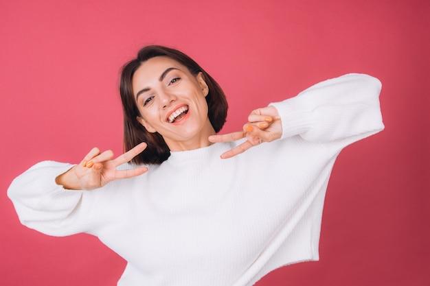 Красивая женщина в повседневном белом свитере, улыбается жестом победы