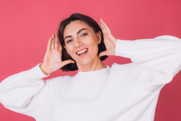 Красивая женщина в повседневном белом свитере, счастливая взволнованная движется с улыбкой на лице