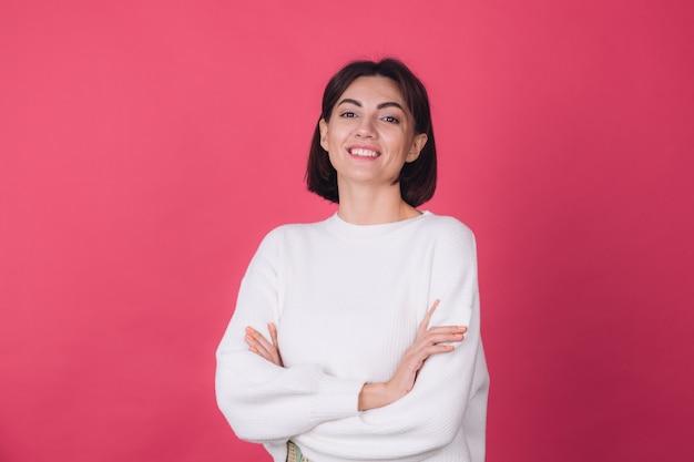 赤い壁にカジュアルな白いセーターの美しい女性