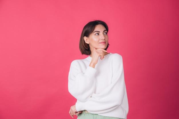붉은 벽에 캐주얼 흰색 스웨터에 아름 다운 여자