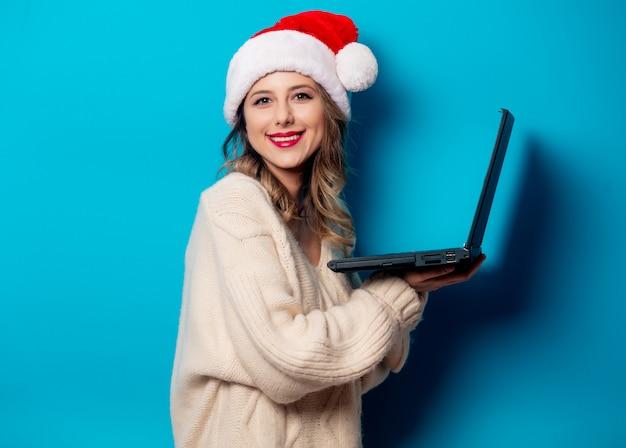 파란 벽에 노트북 컴퓨터와 크리스마스 모자에서 아름 다운 여자