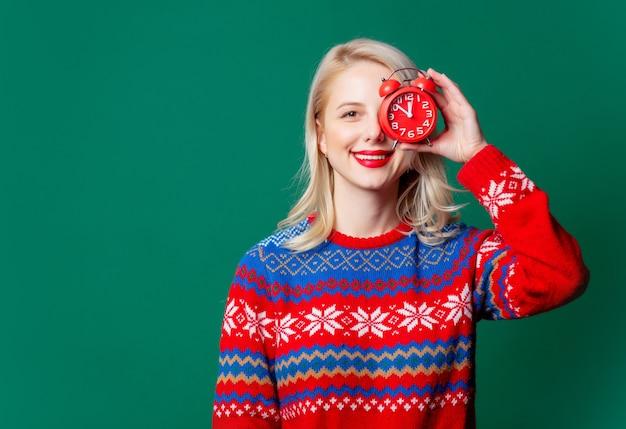 알람 시계와 함께 크리스마스 스웨터에서 아름 다운 여자