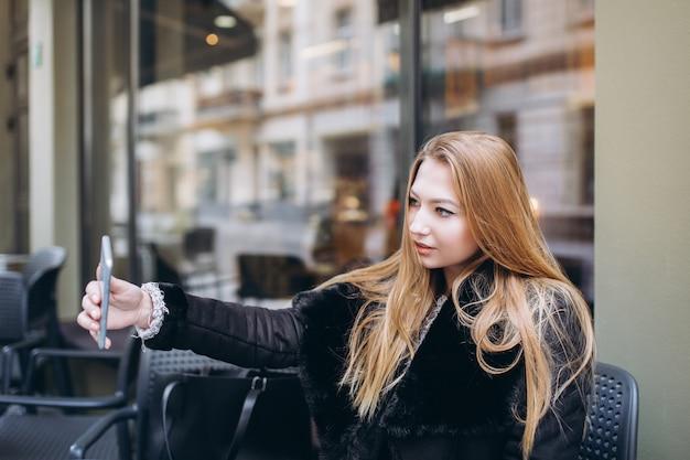 Красивая женщина в городе с смартфон делает селфи