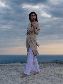 ビーチの新鮮な空気のエレガントなスタイルのポーズをとるコートの美しい女性