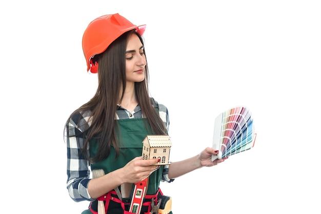 Красивая женщина в комбинезоне с инструментами и образцом цвета