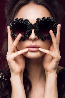 Красивая женщина в темных очках, с локонами и вечерним макияжем