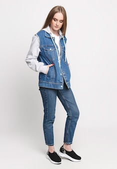 Красивая женщина в джинсовом свитере и джинсах на белом фоне. фото-концепция рекламы джинсов. красивая фотомодель.