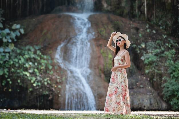 滝のそばのドレスで美しい女性