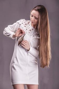 드레스 elegantem에서 아름 다운 여자입니다. 회색 표면에 유행 옷 모델