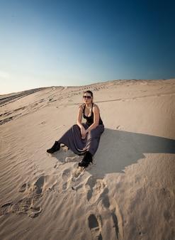 Красивая женщина в платье, сидя на песчаной дюне