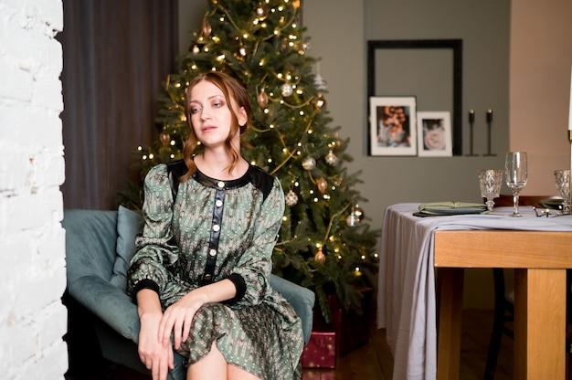 部屋の豊かなインテリアで豪華なクリスマスツリーを背景にエレガントなドレスの美しい女性