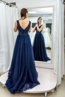 カメラにポーズをとってエレガントなイブニングドレスの美しい女性