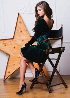 エレガントなグリーンのベルベットのドレスのポーズで美しい女性