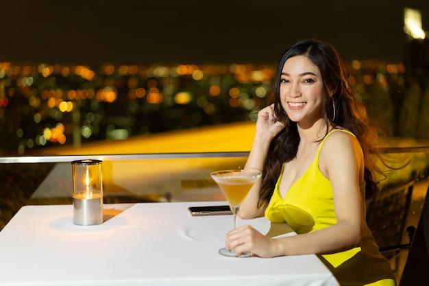 Красивая женщина в вечернем платье, держащая коктейль в ресторане над ночным городом