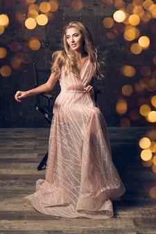 자에 앉아 이브닝 드레스에 아름 다운 여자