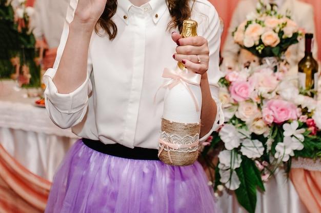 パーティーでポーズをとってシャンパンを保持するファッションドレスの美しい女性。