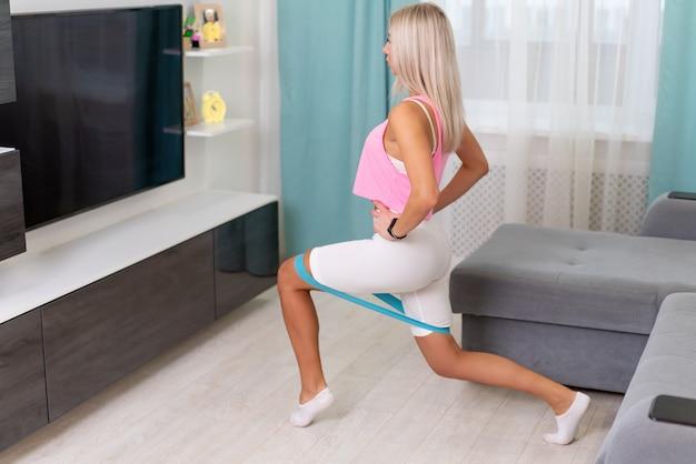 Красивая женщина в спортивной одежде моды делать упражнения с желтой полосой дома. концептуальные домашние тренировки