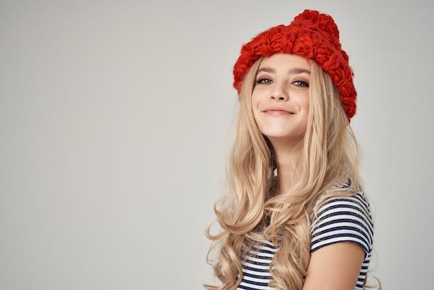 ファッショナブルな服を着た美しい女性赤い帽子明るい背景。高品質の写真