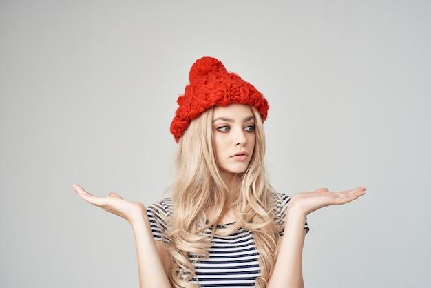 ファッショナブルな服を着た美しい女性赤い帽子明るい背景のライフスタイル