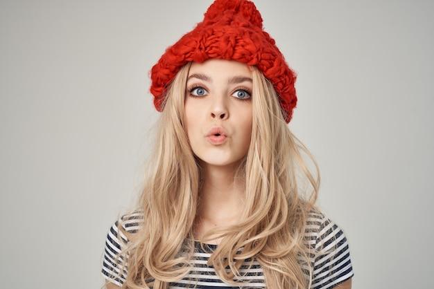 ファッショナブルな服を着た美しい女性赤い帽子ポーズスタジオ