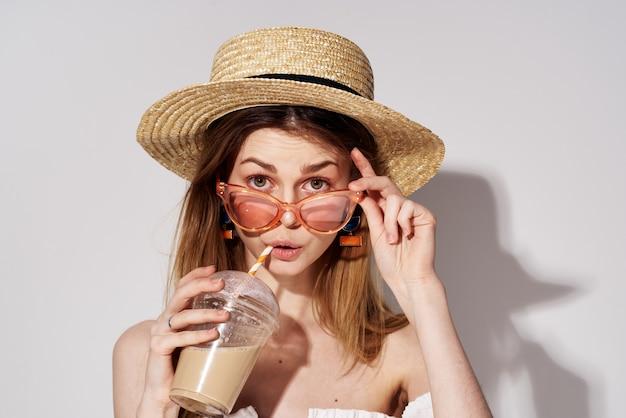 ファッショナブルなメガネと帽子の装飾チャームドリンクモデルの美しい女性